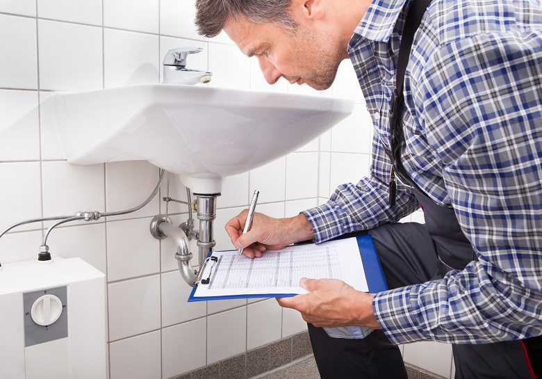 Close-up Of Plumber Standing In Front Of Washbasin Writing On Clipboard